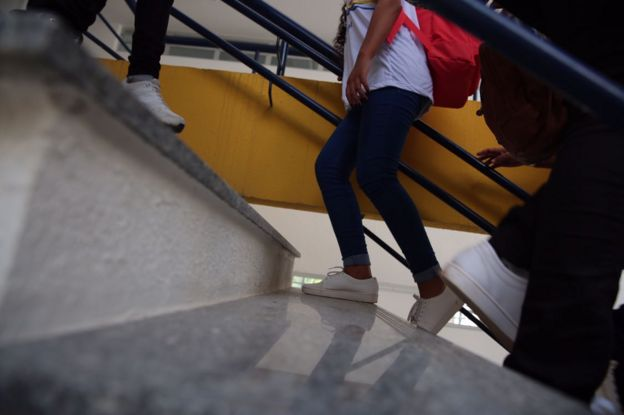 Adolescente com mochila nas costas sobe escadas em instituição de ensino