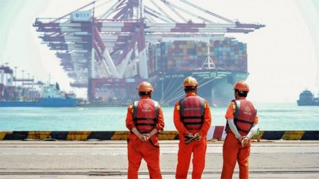 Dock workers in China watch a container ship