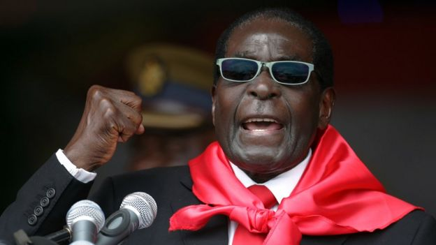 Robert Mugabe, wearing a bright red scarf and sunglasses, raises a fist