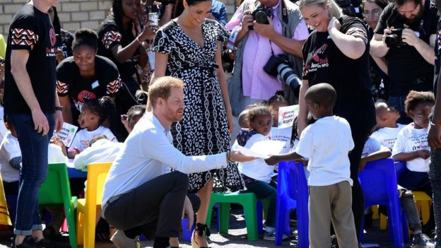 Prince Harry is presented with a drawing by a young boy
