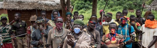 In this photograph taken on August 16, 2017, anti-Balaka combatants patrol in the parish of Gambo, south-eastern Central African Republic. On 13 May 2017, dozens of anti-Balaka fighters stormed the city of Bangassou. They killed dozens of Muslim civilians. Since then, the administration and a large number of residents have fled the city.