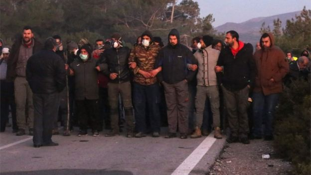 Demonstrators try to block a road in Lesbos