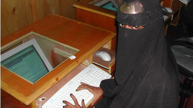 A woman wearing a niqab types at a computer in an internet cafe in Somalia