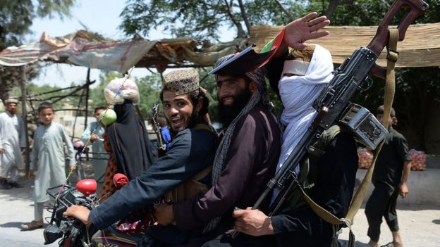 Afghan Taliban militants ride a motorbike as they celebrate a ceasefire on the outskirts of Jalalabad on June 16, 2018
