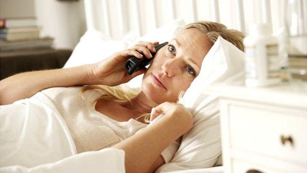 Mujer postrada en la cama hablando por teléfono