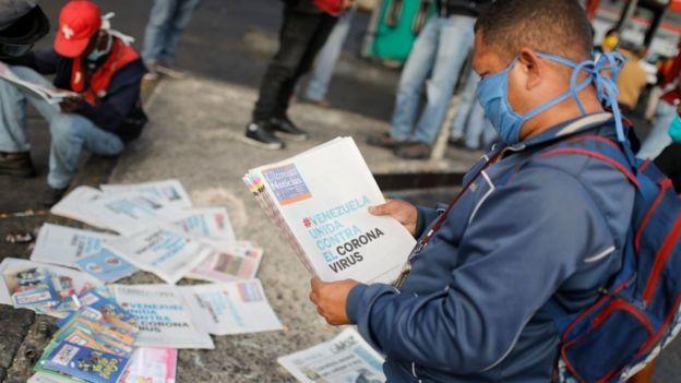 Un hombre lee la prensa en Venezuela en marzo con una mascarilla.