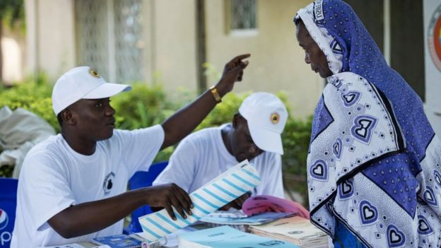 A Tanzanian woman is helped by an electoral agent on where to cast her vote for the Tanzanian presidential elections at a polling station on October 25, 2015 in Dar es Salaam