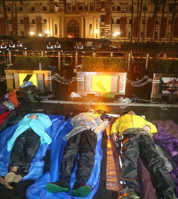 警方在7日凌晨強拆帳篷,預備下一波驅離動作,黃國昌(右)與徐永明(中)等人繼續躺在雨中。