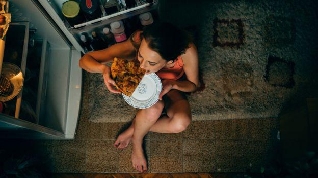 Une jeune femme cède à son envie de pizza