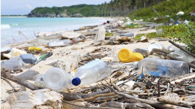 Imagem mostra praia poluida com garrafa e outros materiais de plástico