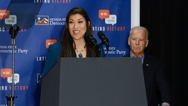 Lucy Flores speaking at a 2014 Nevada campaign event with Joe Biden behind her