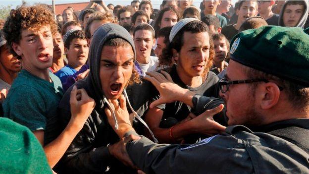 Israelenses brigam com as forças de segurança israelenses na Cisjordânia ocupada em junho de 2018
