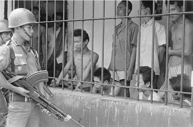 Serdadu mengawasi para tersangka Komunis yang ditahan di sebuah lokasi di Tengerang, oktober 1965