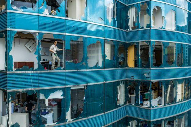 Tayfun nəticəsində ziyan çəkən bir binanın sınıq penceresində dayanan kişi
