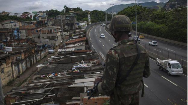 Militar observa a Cidade de Deus durante operação