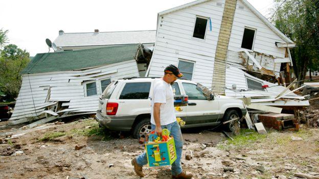 Un hombre pasa frente a una casa destruida por el Huracán Irene en Prattsville, Nueva York
