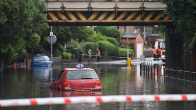 A car stranded in flood water in Crossley Road in Manchester
