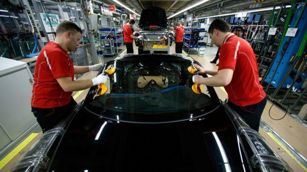 Trabajadores en una fábrica de autos.