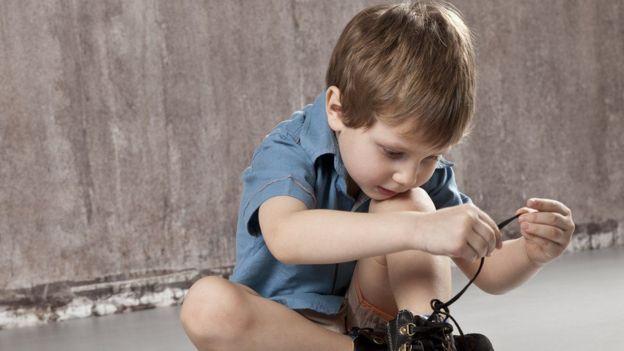 Niños atándose los cordones.