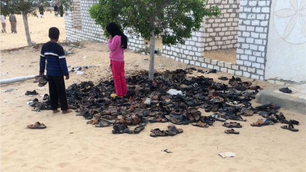 Egyptian children stand near a pile of footwear belonging to the victims of the Rawda mosque attack, Egypt, 25 November 2017