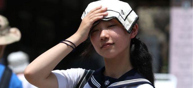 Pelajar Jepang memakai sapu tangan melindungi diri dari panas matahari