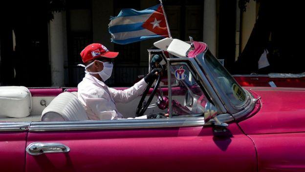 Un hombre con mascarilla manejando un auto antiguo en Cuba