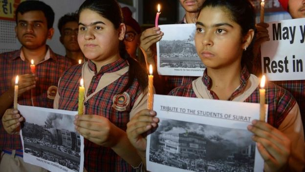 Indian students hold candles as they pay tribute to the students died in a fire in a building in India housing a college in Surat, at a school in Amritsar on May 25, 2019