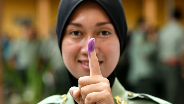 A Malaysian Army forces shows her inked finger after casting her vote during an early vote for the 14th general election in Kuala Lumpur on May 5, 2018