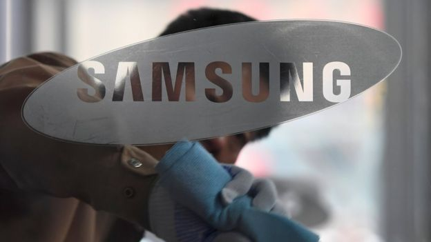 A man cleaning a glass with the Samsung logo.