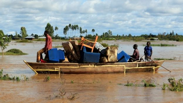 Residents use a boat to carry their belongings through the waters after their homes were flooded as the River Nzoia burst its banks