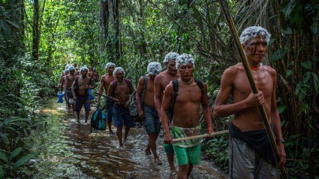 Guerreiros Yanomami cruzam riacho durante um encontro de lideranças na comunidade watoriki, na Terra Indígena Yanomami, em novembro de 2019
