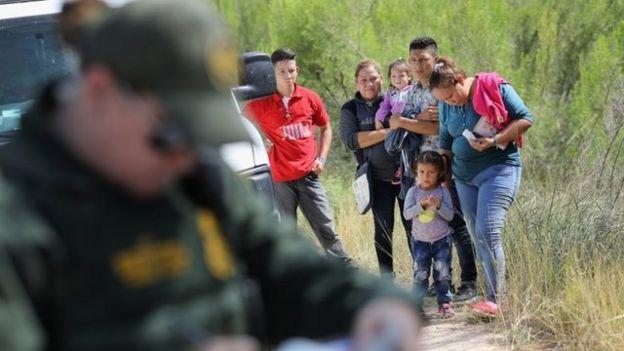 Pessoas aguardam para ser levadas em custódia na fronteira, perto de McAllen, no Texas