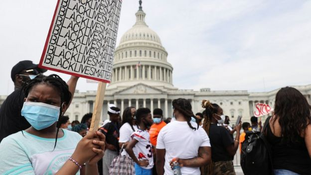 "A young protester holds up a sign saying ""Black Lives Matter"" near the US Capitol in Washington (6 June 2020)"