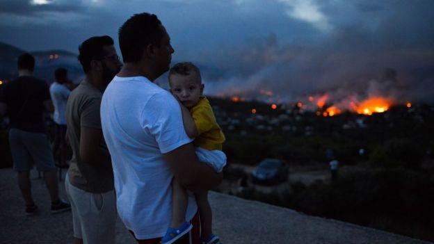Un grupo de personas observa el incendio forestal cerca de Atenas el 23 de julio de 2018.