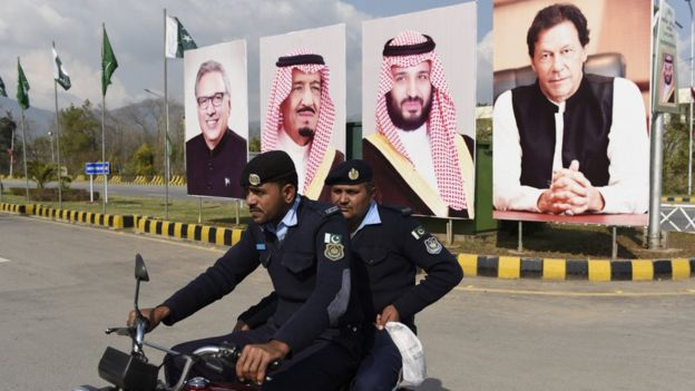 Policemen in front of large posters of Imran Khan and MBS