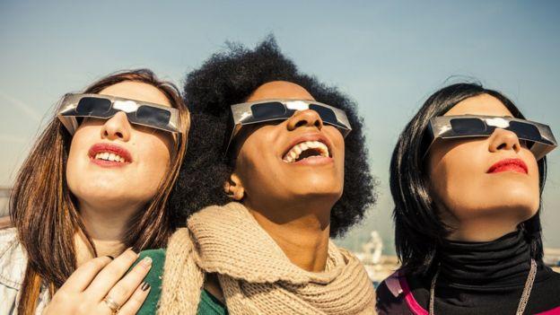 Jóvenes mirando un eclipse