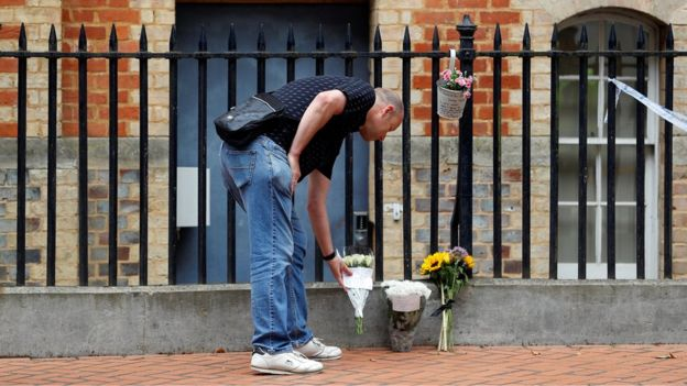 A man placing a floral tribute at Forbury Gardens in Reading