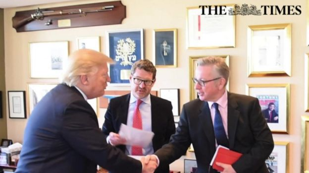 Mr Trump shaking hands with Michael Gove during the interview.