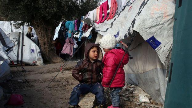أطفال يلعبون أمام خيمة