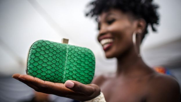 Model holds a green fish skin clutch