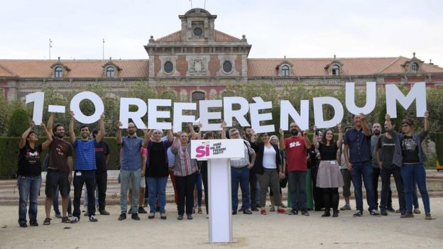 Members of the Catalan pro-independence movement hold a placard alluding to the referendum vote on 1 October