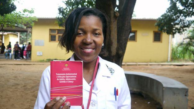 Mulher moçambicana segura um livreto rosa, onde está escrito: 'Tratamento Antiretroviral e Infecções Oportunistas'.