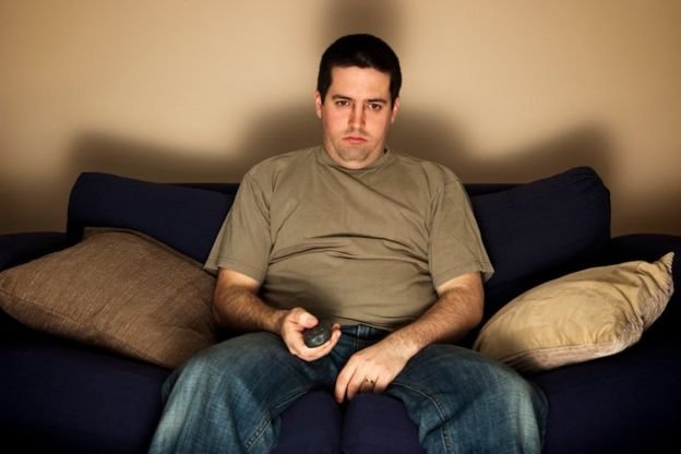 Hombre mirando televisión en el sofá.