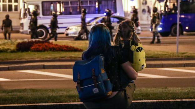 Женщина с ребенком наблюдают за акцией протеста в Минске 10 августа