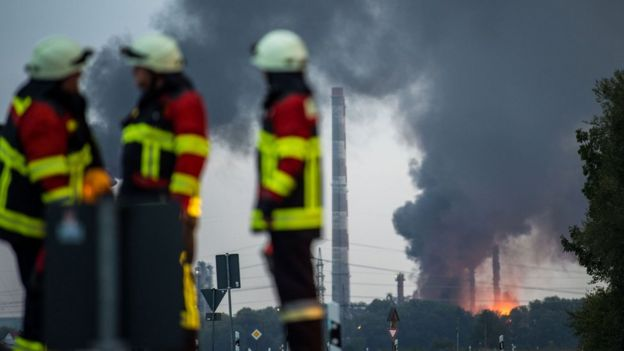 Firefighters stand next to the site of a refinery of Bayernoil company where the explosion took place