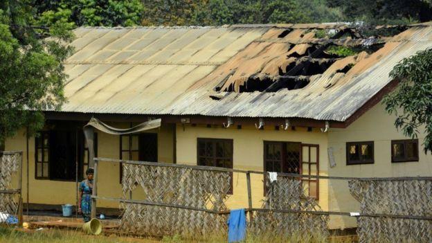 Una mujer frente a un colegio destruido.