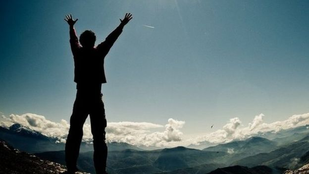 Man on top of a mountain, arms raised, sun rising