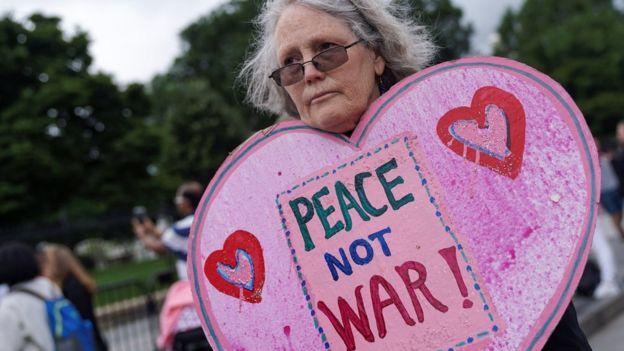 """Una mujer con un cartel de """"Paz, no guerra"""""""