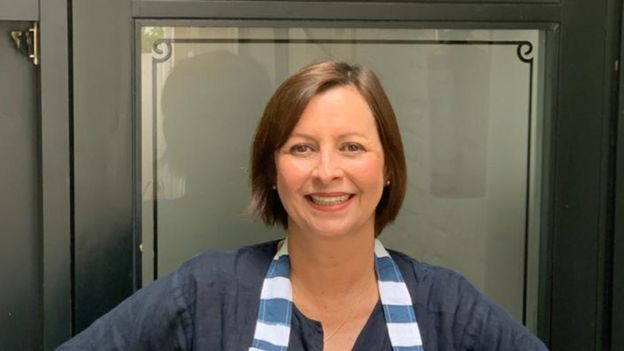 A chef Carla Pernambuco sorrindo para a foto e usando um avental