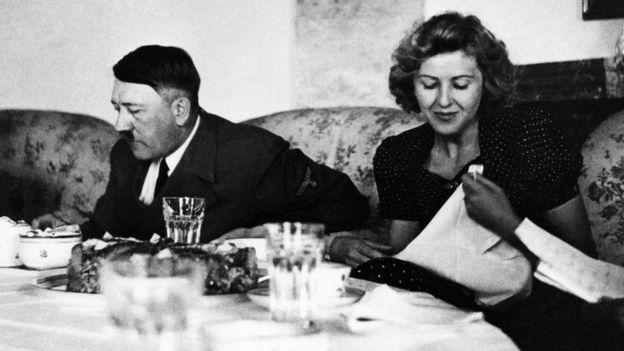 Hitler sentado em uma mesa comendo com uma mulher ao lado